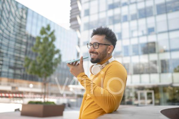 Man with eyeglasses sending voicemail through smart phone in city