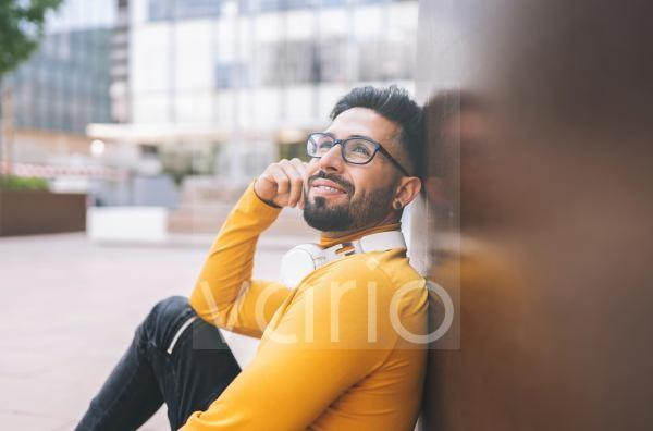 Smiling bearded man day dreaming while leaning on wall