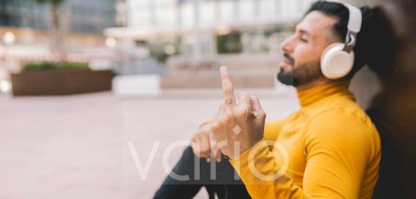 Man showing obscene gesture while leaning on wall