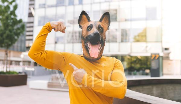 Man with dog mask flexing muscle in city