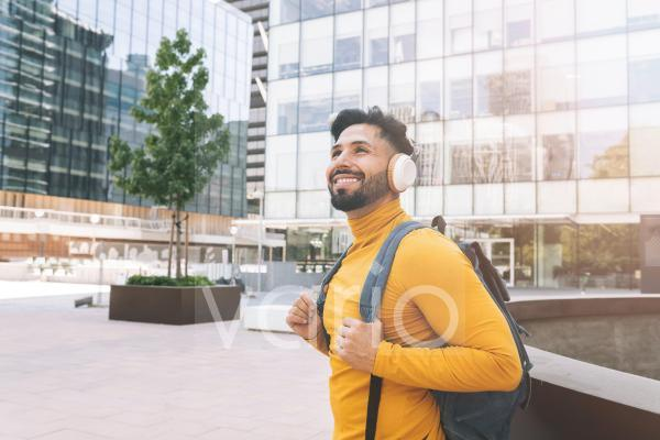 Smiling man with headphones and backpack in city
