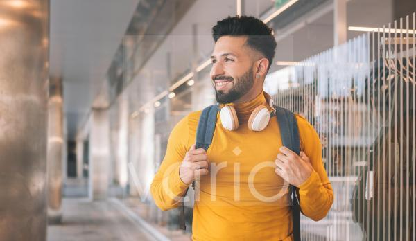 Man with headphones and backpack standing by glass wall