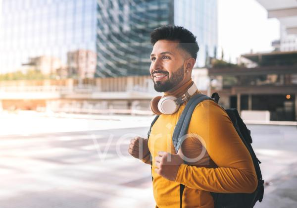 Smiling man with headphones and backpack