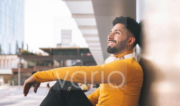 Happy bearded man leaning on wall