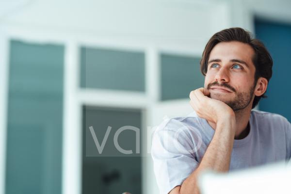 Thoughtful man with hand on chin at home