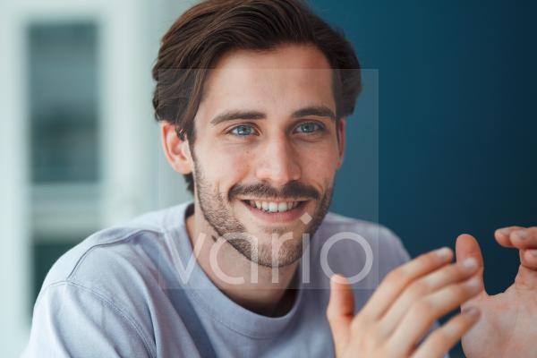 Smiling young man gesturing at home