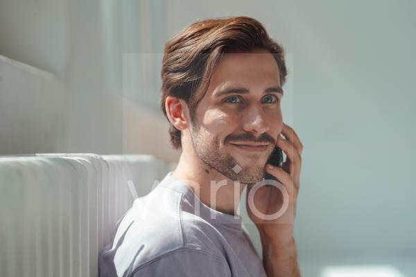 Smiling man talking on mobile phone at home