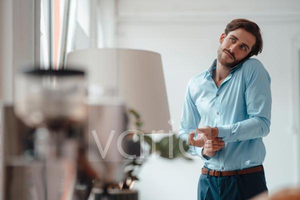 Businessman talking on mobile phone while buttoning shirt in office
