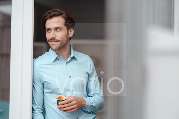 Businessman with disposable coffee cup leaning on door
