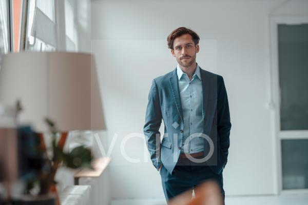 Businessman with hands in pockets at office