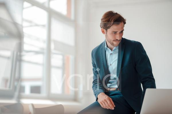 Male professional using laptop while working in office