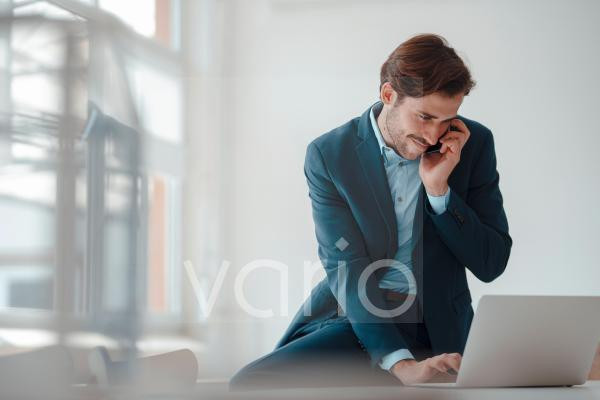 Young businessman using laptop while talking on mobile phone in office