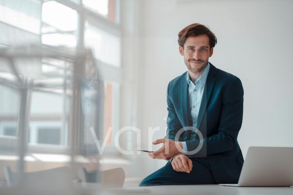 Smiling businessman with mobile phone sitting in office