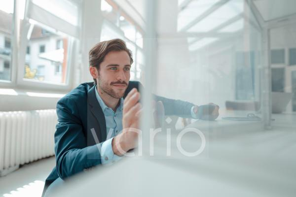 Male professional looking at glass box in office