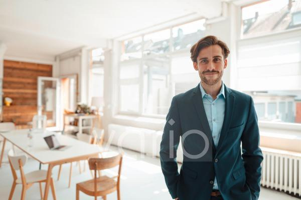 Male professional with hands in pockets standing at office