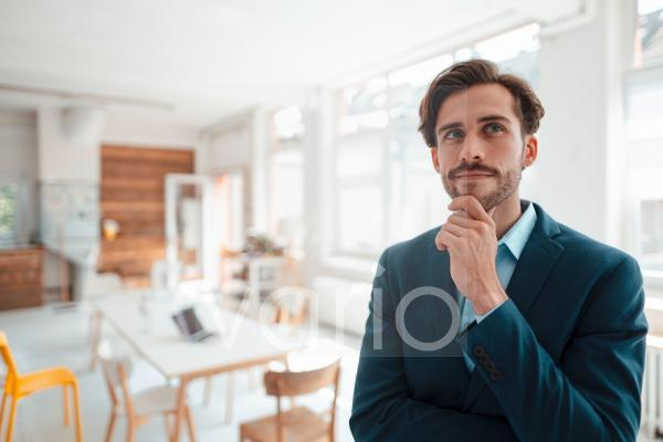Thoughtful businessman with hand on chin in office