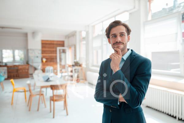 Male professional with hand on chin in office