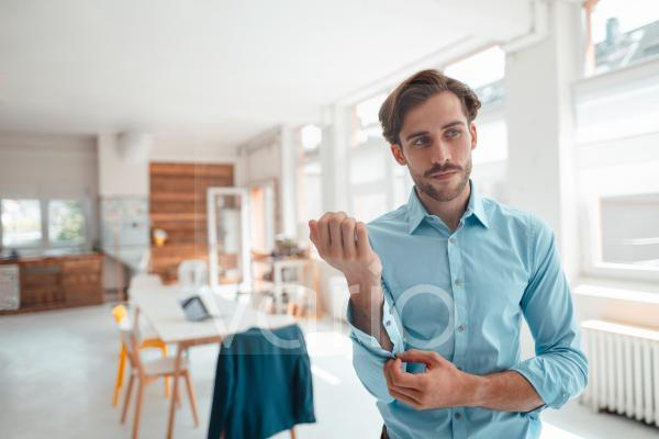 Businessman unbuttoning sleeve while standing in office