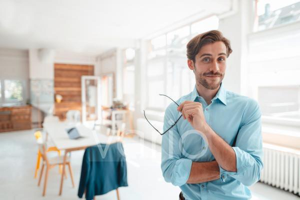 Male business professional with eyeglasses in office