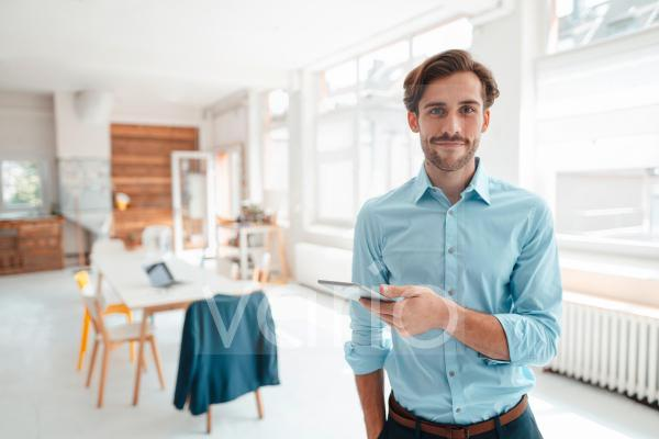 Male business professional with digital tablet at office