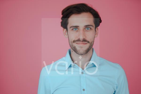 Smiling businessman against pink background