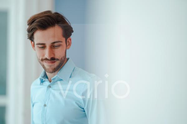 Young businessman with hair stubble wearing blue shirt