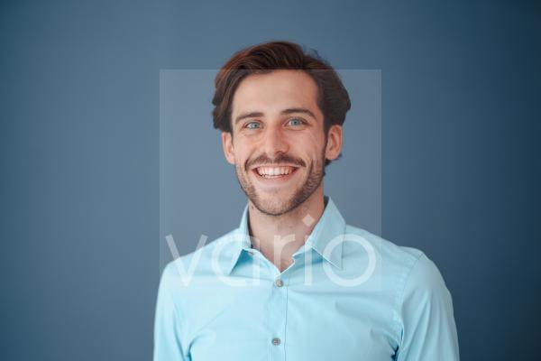 Happy businessman against blue background