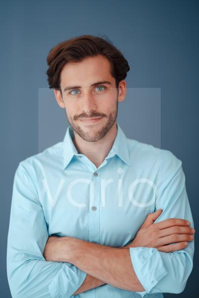 Young businessman with arms crossed against blue background