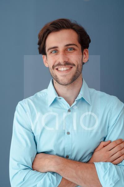 Smiling businessman with arms crossed against blue background
