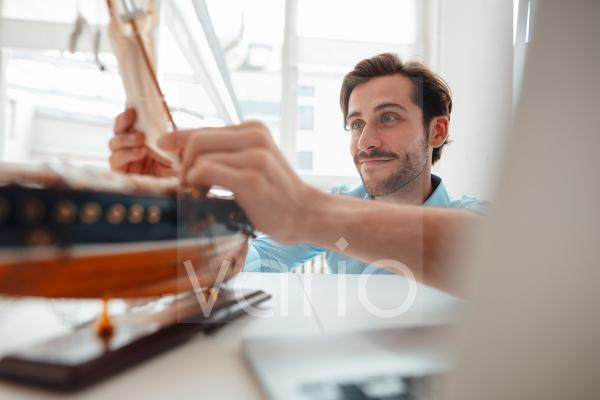 Businessman adjusting mast on toy boat in office