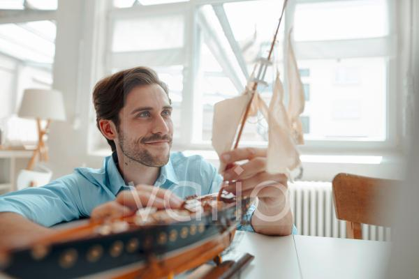 Male businessman looking at mast on toy boat in office