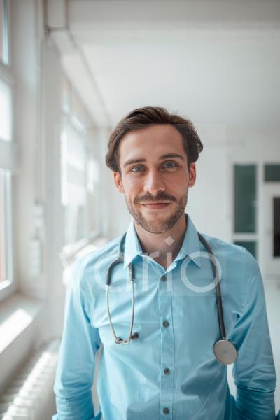 Smiling male doctor with stethoscope in office