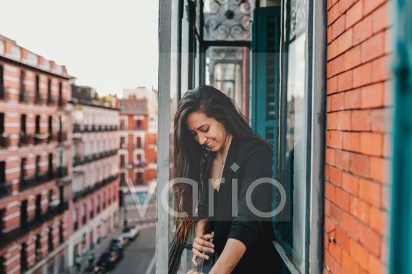 Young smiling woman standing at window