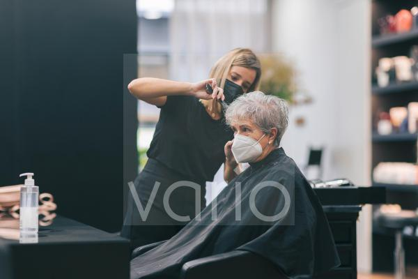 Female hairdresser cutting hair of customer in salon during COVID-19