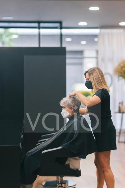Female hair professional with face mask standing behind customer in salon