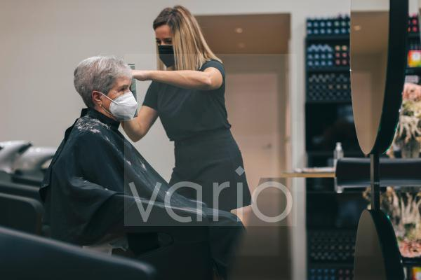 Female hairdresser with face mask cutting customer's hair in salon