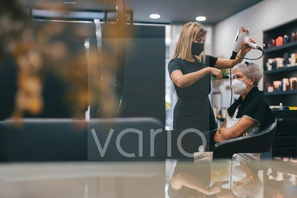 Female hairdresser with face mask blow drying customer's hair in salon