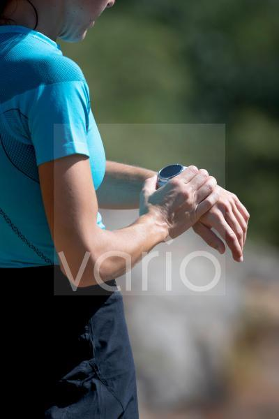 Female athlete checking smart watch on sunny day