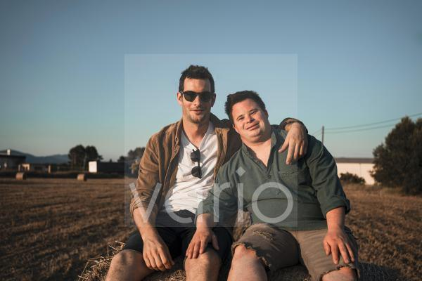 Man wearing sunglasses sitting with friend on bale of straw