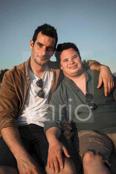 Man sitting with arm around friend at sunset