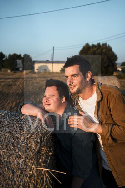 Male friends leaning on bale of straw during sunset