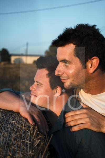 Smiling male friends leaning on bale of straw