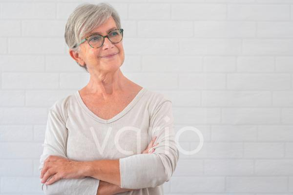 Smiling senior woman contemplating while standing with arms crossed