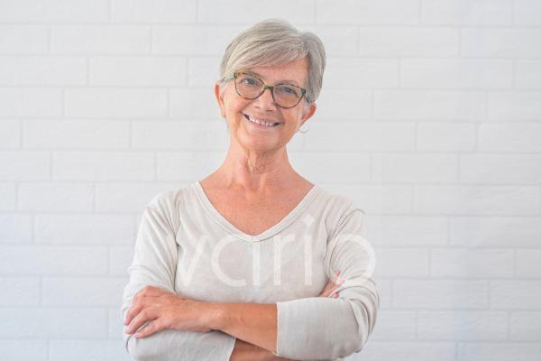 Smiling senior woman with arms crossed in front of white wall