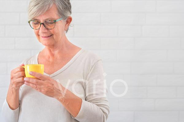 Senior woman holding yellow coffee cup in front of wall