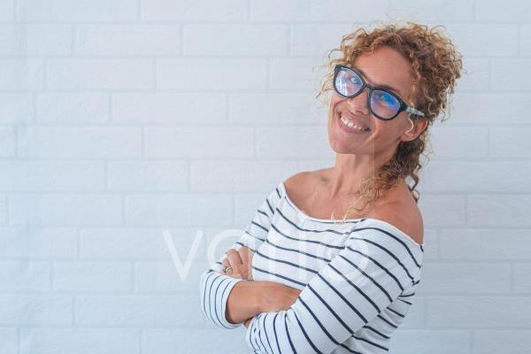 Happy mature woman with arms crossed by wall