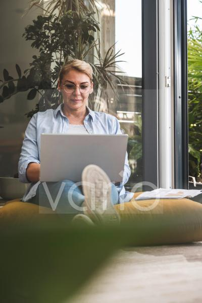 Businesswoman using laptop while sitting at home