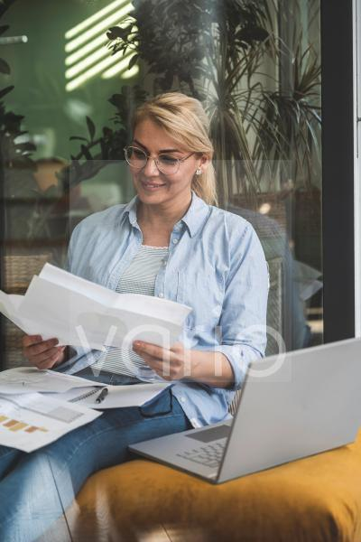 Female freelancer checking documents while sitting with laptop at home