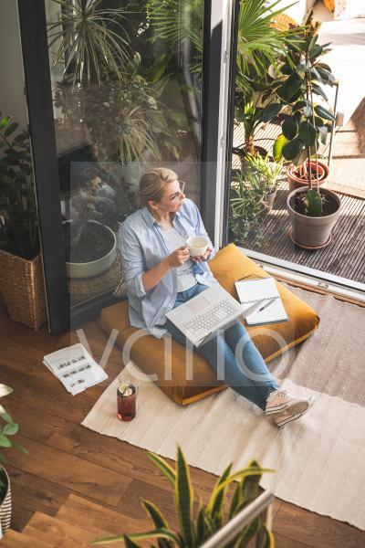 Businesswoman having coffee while sitting with diary and laptop at home
