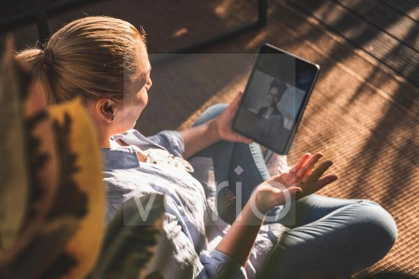 Woman talking with friend on video call through digital tablet on terrace